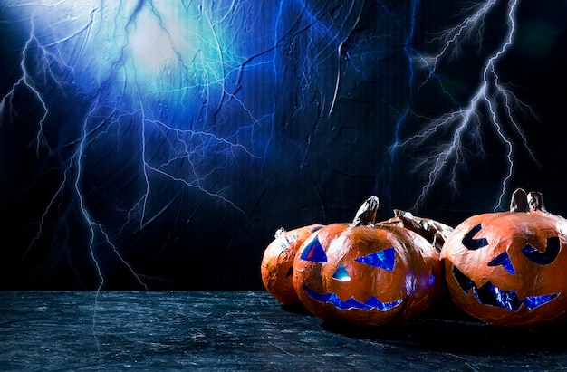 Decorative halloween pumpkin with carved faces and lightning on background Premium Photo