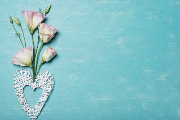 Decorative handmade heart with eustoma flowers against blue textured background Free Photo