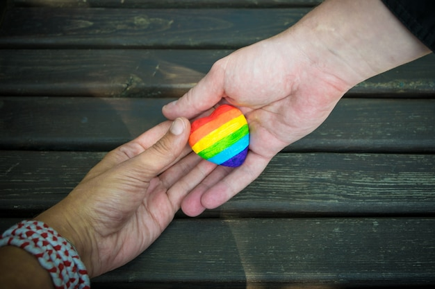Decorative heart with rainbow stripes in male hands. lgbt pride flag, homosexual love, human rights concept. Premium Photo