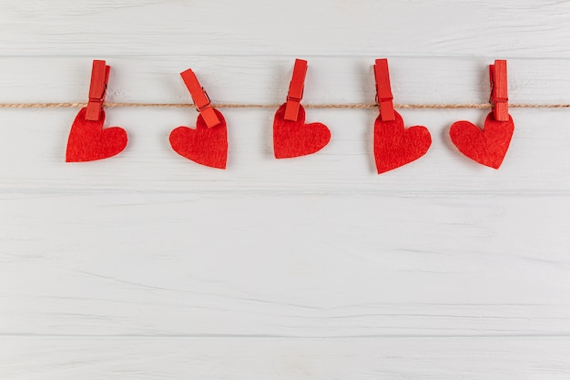 Decorative hearts hanging on rope with pegs Free Photo