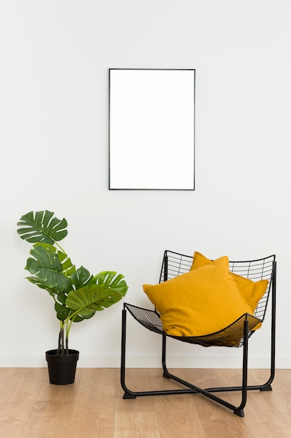 Decorative plant with empty frame and chair Free Photo