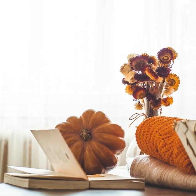装飾的なカボチャ、ドライフラワー、本、暖かいセーター。秋の日の読書。秋の本。秋の読書。居心地の良い気分。 Premium写真