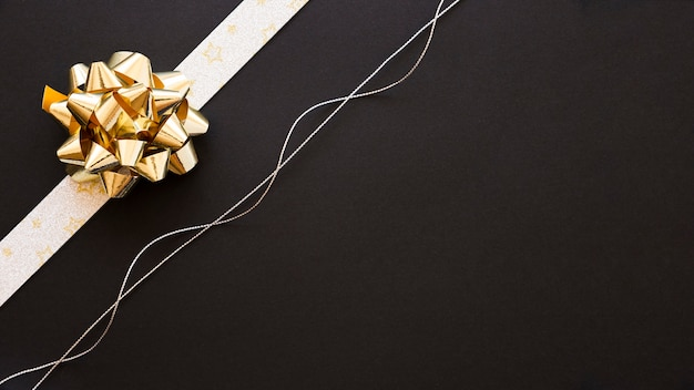 Decorative ribbon bow and silver string on black background Free Photo