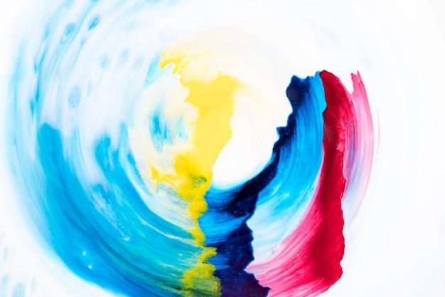 Decorative watercolor brush strokes in circular form over white paper Free Photo