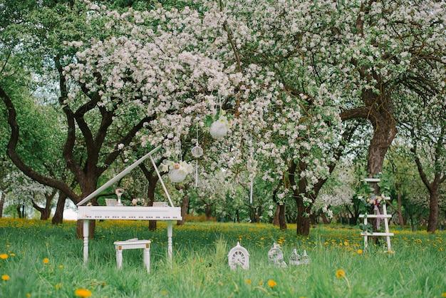 春に咲く庭で装飾的な白い脚立と白いグランドピアノ。ロマンチックな装飾 Premium写真