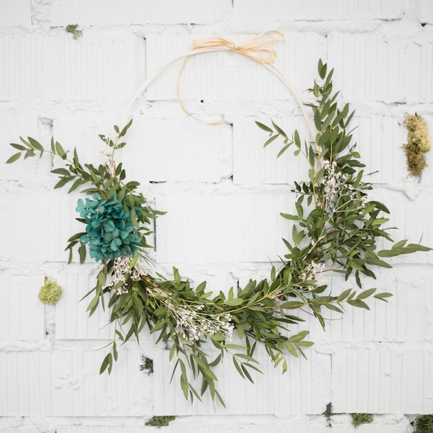 Decorative wreath attached on white brick wall Free Photo