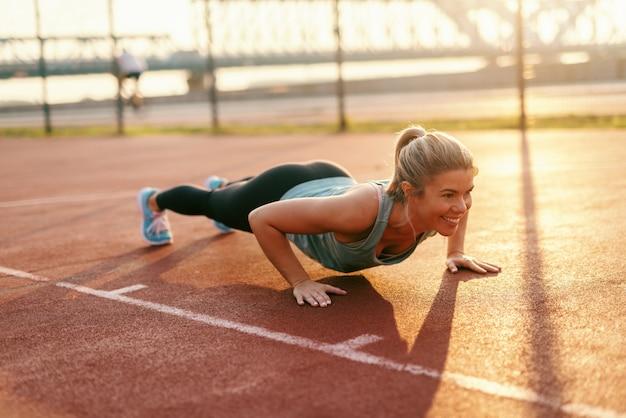ポニーテールと朝のコートで腕立て伏せを行うスポーツウェアに身を包んだ熱心なブロンドの女性。 Premium写真