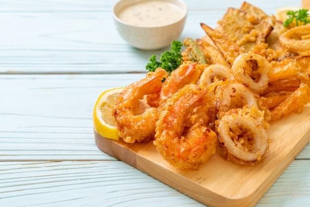 Обжаренные во фритюре морепродукты (креветки и кальмары) с овощным миксом - нездоровый стиль питания Premium Фотографии