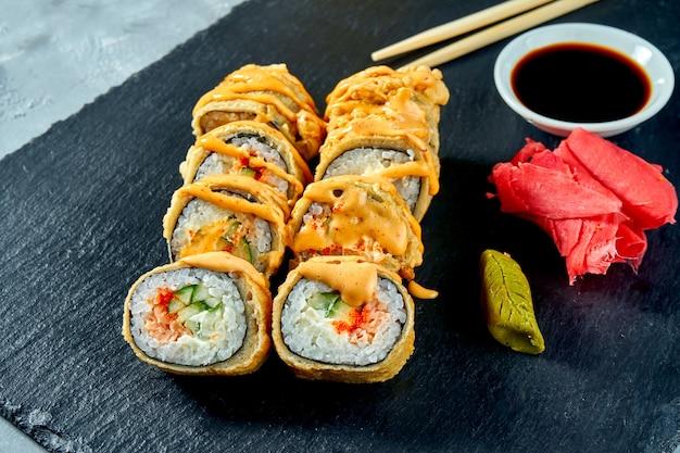 サーモンとキュウリの天ぷらを黒いスレート板に巻き揚げた寿司。セレクティブフォーカスセレクティブフォーカス Premium写真