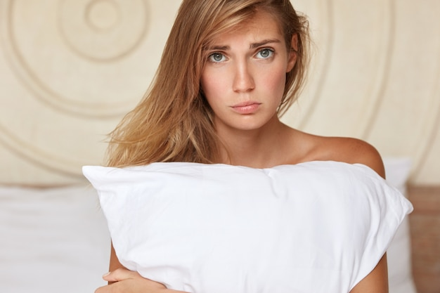 Deeply upset young woman sits on bed at home, feels lonely and sad, suffers from insomnia, embraces pillow or has some disagreement with boyfriend after spending night together. sleepless concept Free Photo