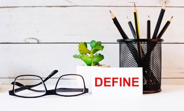 Define written on a white business card next to pencils in a stand and glasses. nearby is a potted plant. Premium Photo