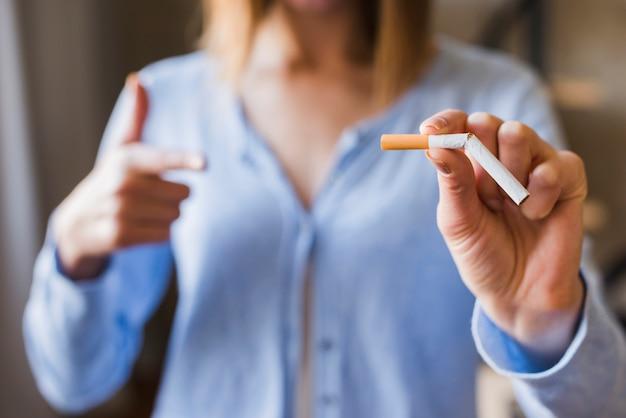 Расфокусировать женщина, указывая на сломанную сигарету Бесплатные Фотографии