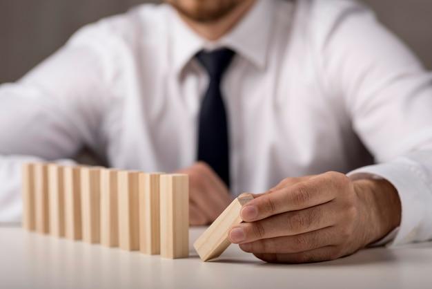 Defocused businessman in suit and tie with dominoes Free Photo