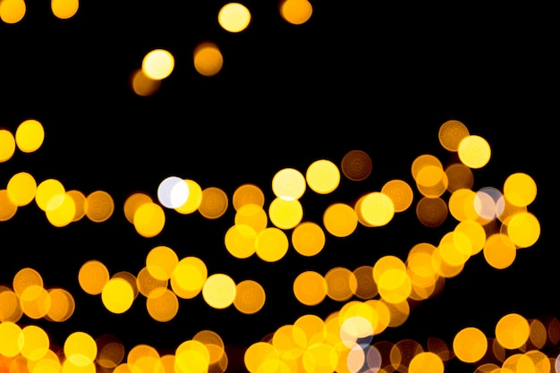 Defocused city gold night bokeh abstract background. blurred many round yellow light on dark background Premium Photo