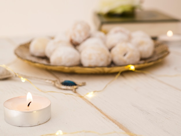 Defocused cookie plate with candle and quran Free Photo