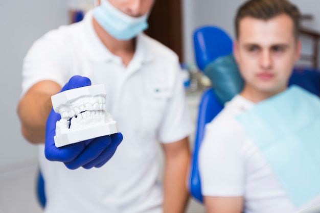 Defocused dentist holding dentures with patient Free Photo