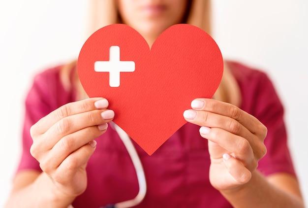 Medico femminile defocused che tiene cuore di carta Foto Gratuite
