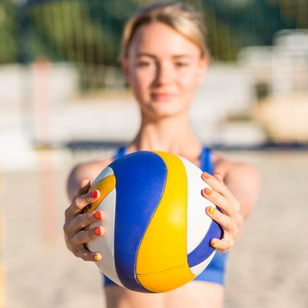Giocatore di pallavolo femminile defocused sulla sfera della holding della spiaggia Foto Gratuite