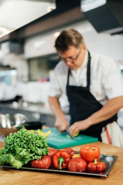 Verdure di taglio del cuoco unico maschio defocused Foto Gratuite