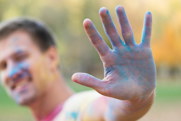 Defocused man showing blue hand at festival Free Photo