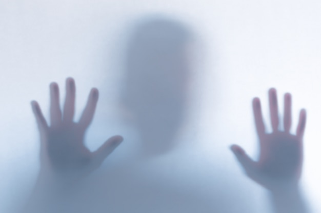 Defocused scary ghost silhouette behind a white glass Premium Photo