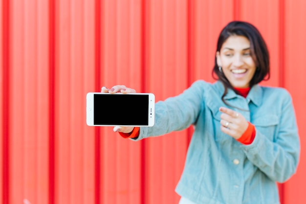 Defocused smiling woman showing cell phone Free Photo