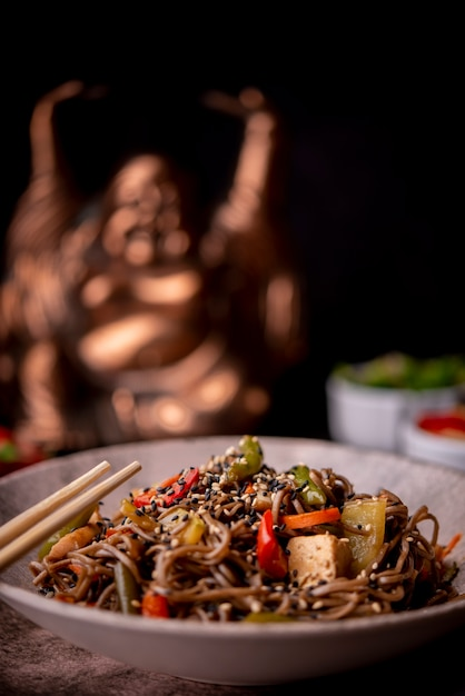 Defocused statue with bowl of noodles with vegetables Free Photo