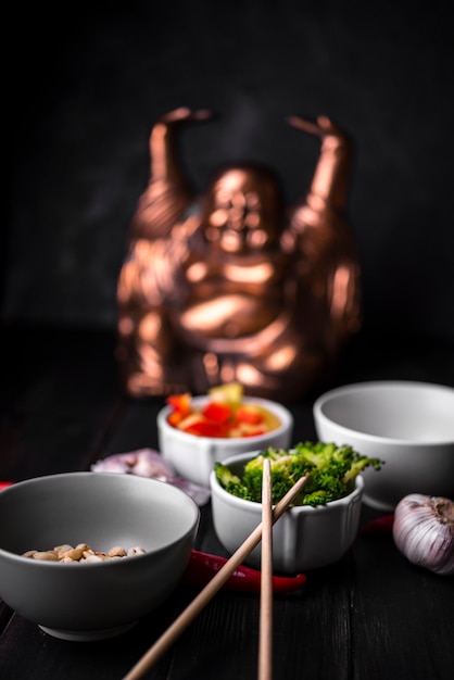 Defocused statue with cups of vegetables and chopsticks Free Photo