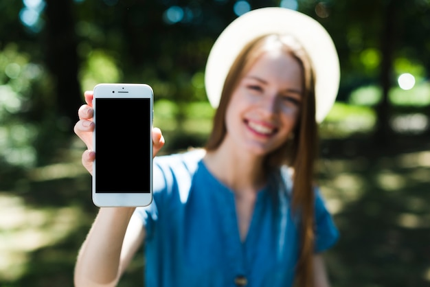 Defocused woman holding mockup smartphone Free Photo