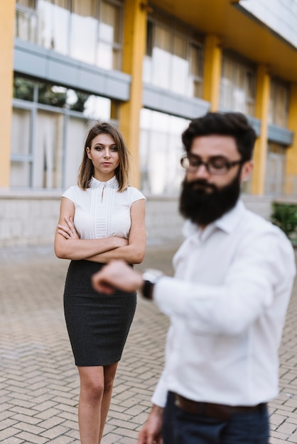 Defocused young businessman looking at wrist watch with stylish young woman standing in the background Free Photo