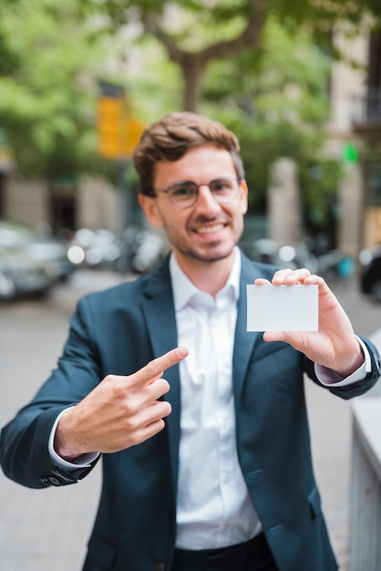 Defocussed young businessman pointing his finger toward visiting card Free Photo