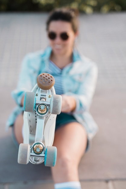 Defocussed young woman showing foot with roller skate Free Photo