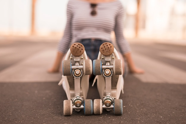 Defocussed young woman sitting on ground with roller skate on her feet Free Photo