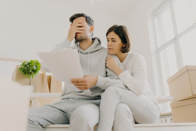 Dejected husband and wife manage finances, receive bill, face financial problem, have gloomy expressions, sit together in empty room, big window behind, cardboard boxes with personal stuff near Premium Photo