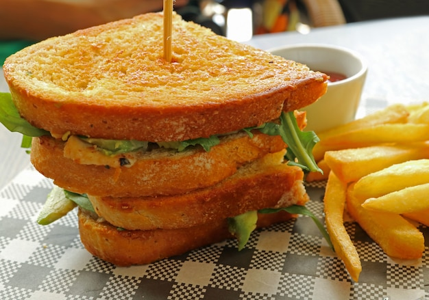 Delectable chicken avocado salad sandwich with french fries Premium Photo