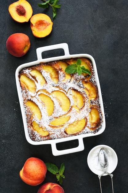 コンクリートの黒い背景に粉砂糖をまぶした桃と繊細なケーキ Premium写真