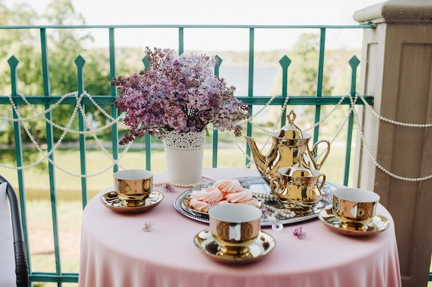 ピンクのテーブルクロスが付いたテーブルの上にライラックの花、アンティークのスプーン、皿が置かれた繊細なモーニングティーテーブルのセッティング。 Premium写真