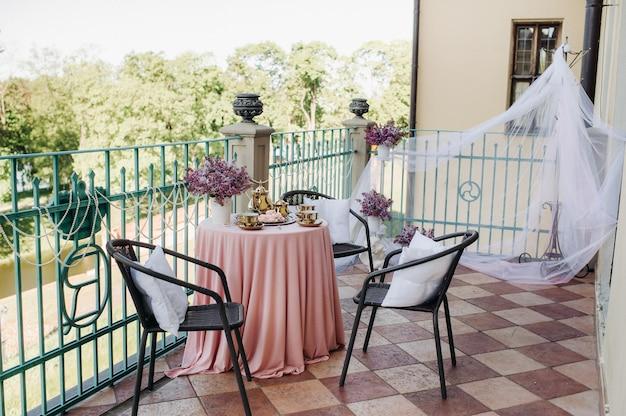 ネスヴィジ城のライラックの花、アンティークのスプーン、ピンクのテーブルクロスをかけたテーブルの皿など、繊細なモーニングティーテーブルのセッティング。 Premium写真