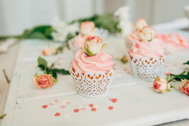 Delicate tasty muffins with a pink cream decorated with real ros Premium Photo