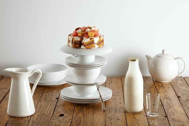 Нежный белый чайный сервиз, бутылка молока и аппетитный бисквит с шоколадом, сливками и грейпфрутами Бесплатные Фотографии