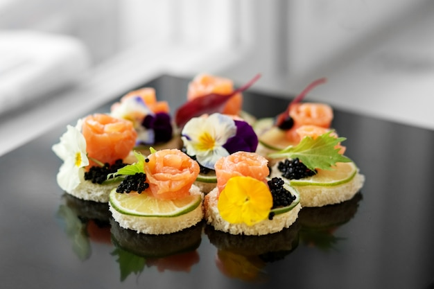 Delicious appetizer with salmon and edible flowers. Premium Photo