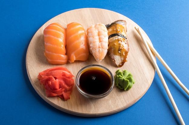 Аппетитный аппетитный суши-нигири сервируется на деревянных тарелках с соевым соусом и палочками для еды. квартира лежала на синем столе Premium Фотографии