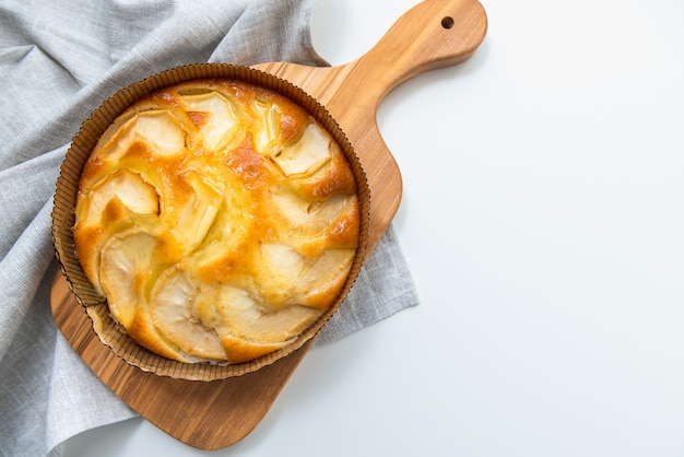 Delicious apple pie on wooden board, on white background with copy space, top view. Premium Photo