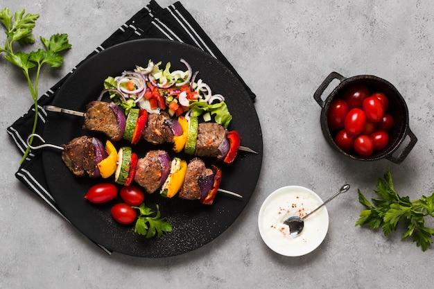Вкусные арабские шашлычки из фаст-фуда на черной тарелке и помидорах Бесплатные Фотографии