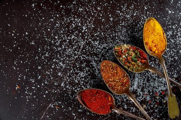 Delicious assortment ground spice ingredients on dark wooden background Premium Photo