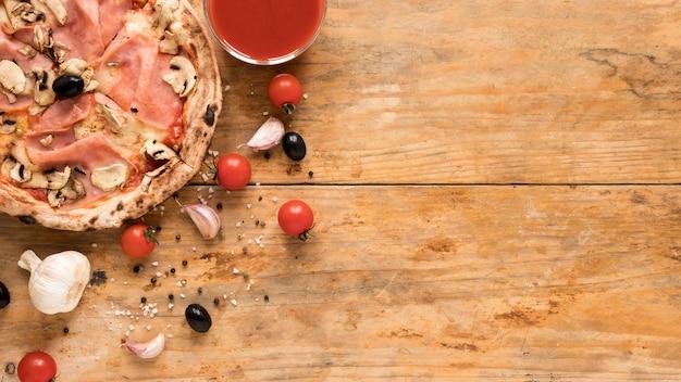 Delicious bacon; mushroom pizza near garlic; cherry tomato; black olive and bowl of tomato sauce over wooden desk Free Photo