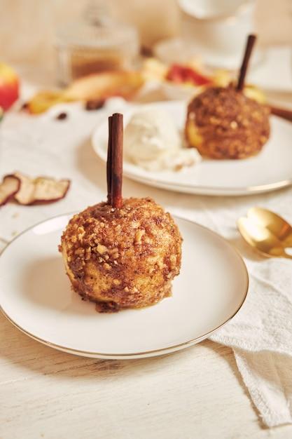 흰색 테이블에 크리스마스 견과류와 계피와 함께 맛있는 구운 사과 무료 사진