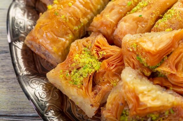 Delicious baklava dessert in oriental bronze setting close up Premium Photo