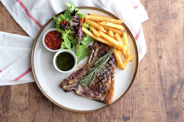 Delicious beef steak with french fries and chilli sauce Premium Photo