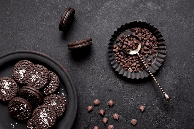 Delicious biscuits with cream and chocolate chips flat lay Free Photo